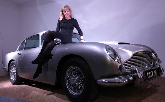 Aktris Britt Ekland berposes dan Aston Martin DB5 yang digunakan James Bond dalam film Goldfinger.